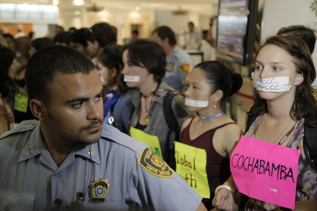 Protesters getting kicked out of the UN Climate Conference, 16TH SESSION OF THE CONFERENCE OF THE PARTIES (COP 16), . Their taped mouths represent their voices being silenced. Photo © Tristan Bayer www.earthnative.com. From the documentary film Revolution